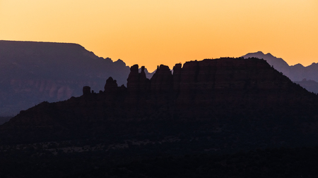 The orange sky with the setting sun behind the Cockcomb mountain.  Taken from Airport Mesa Overlook. Stock Photo