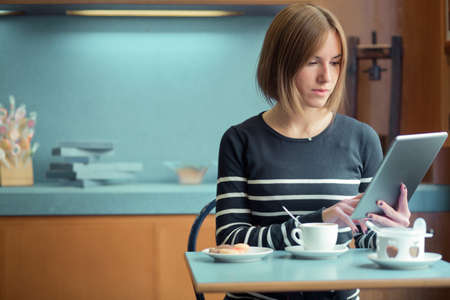 Young girl eating breakfast while working with a tablet in a cofee shop  photo