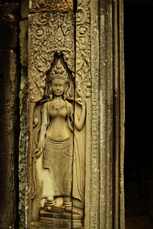 Graceful female figure carved in a stone-bas relief on an ancient Angkorian temple in Angkor Wat, Cambodia. A female spirit of the clouds and water in Hindu and Buddhist mythology. photo