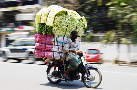 convey: Skillful motorbike driver with a big stack of vegetables, on the streets of Phnom Penh, Cambodia