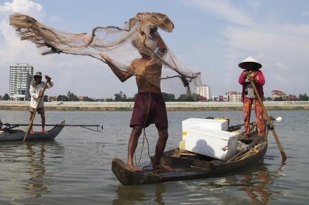 phnom penh: Fisherman and his wife on a small wooden boat on the Mekong river, Phnom Penh, Cambodia