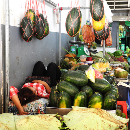 haggling: Market seller relaxing at her stall, surrounded by many watermelons
