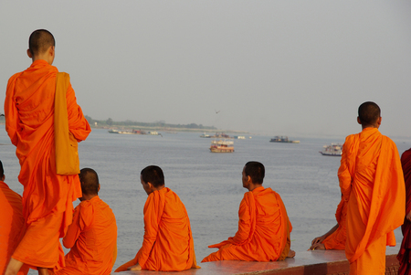 riverfront: Monks in orange sitting and standing along the Mekong riverfront in Phnom Penh, Cambodia, with boats in the background