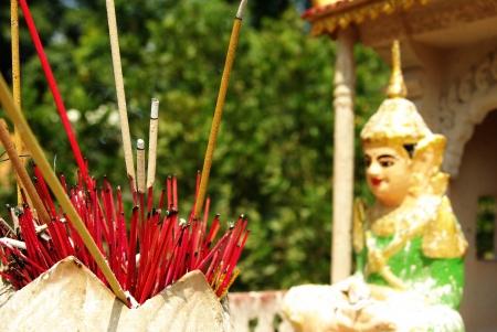 alight: Molti bastoncini di incenso rosso acceso, il rituale spirituale, assemblati in una pentola di terracotta, di fronte a una figura buddista in Asia