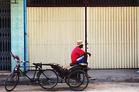 Relaxed bicycle driver waiting in front of a closed gate in Cambodia