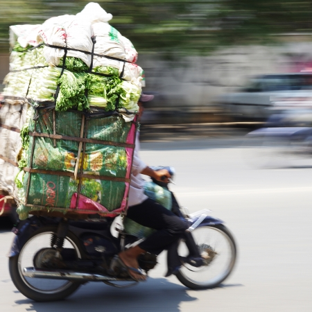 Skillful motorbike driver with a big stack of vegetables, streets of Phnom Penh, Cambodia