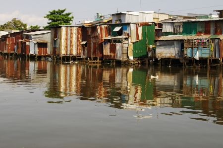 marginalized: The slums along the Mekong river in Saigon, Ho Chi Minh, Vietnam  Mekong Delta  Mirroring in the water  Poor people living in tiny houses made of tin, almost collapsing