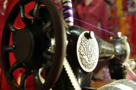 Antique sewing machine, black with silver emblem, purple thread on top photo