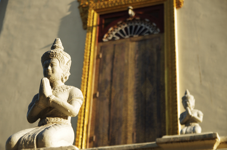 Two Buddha sculptures in front of a buddhist temple in Asia, golden door framing behind photo