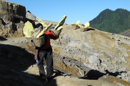Sulfur mining workers on active Ijen volcano crater, Java, Indonesia, carrying loads of blocks in baskets on his shoulder Stock Photo - 25310106