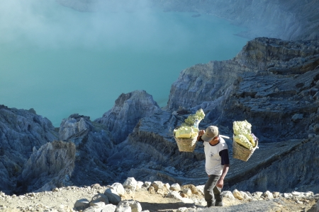 Sulfur worker on active Ijen volcano crater, Java, Indonesia, carrying chunks in a basket on his shoulder Stock Photo - 25294282