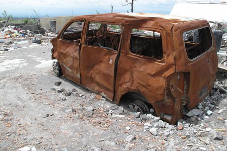 devastation: burnt, Minivan car wreck after volcanic eruption in Indonesia, natural disaster