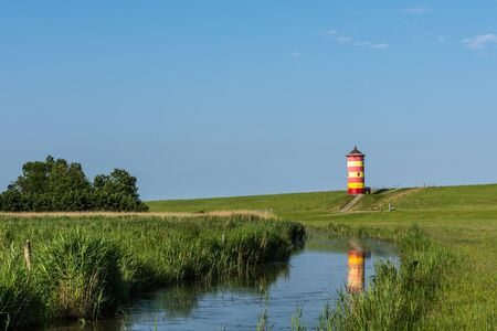 Pilsum Lighthouse with Reflection in Water, East Frisia,Lower Saxony, Germany
