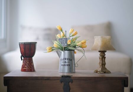 Vase with yellow and green flowers resting on a trunk, with a card that says happy day