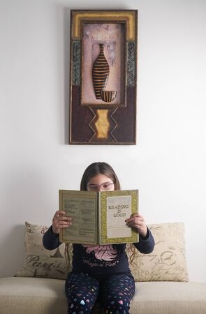 girl reading a book very carefully, the book on its cover says reading is good Stok Fotoğraf