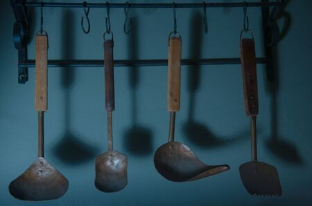 Set of different old spoons hanging on a blue wall