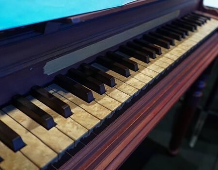 old wooden piano with notoriously aged keys and stained by time