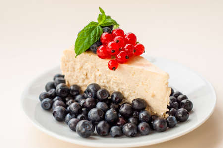 Cheesecake New - York decorated with blueberries, red currants and mint Stock Photo