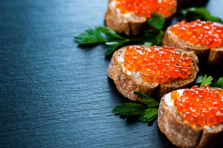 Red caviar on slate background.