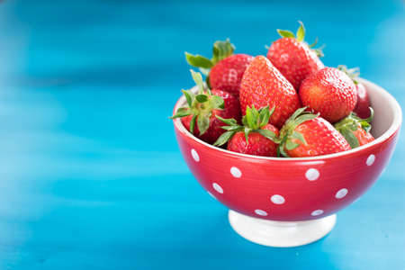 Ripe red strawberries on blue wooden table, Fresh strawberry, Strawberries in white bowl.