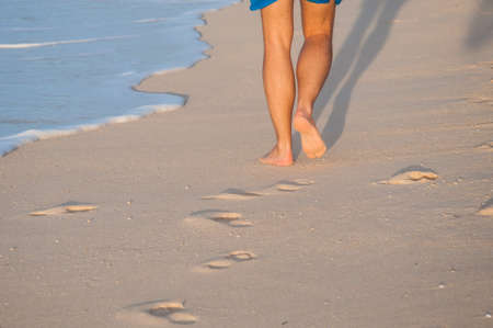 Closeup of a mans bare feet walking at a beach at sunset, with a waves