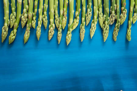 Fresh green asparagus shoots pattern, on a blue wooden background top view