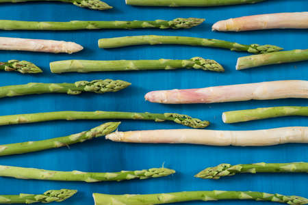 Fresh green, white asparagus shoots pattern, on a blue wooden background top view