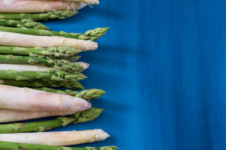 Bunches of green and white asparagus on a blue wooden background top view Banco de Imagens