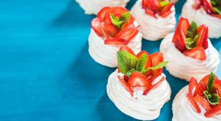 A small meringue Pavlova dessert with some strawberry slices with mint leaves on a blue background