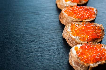 Red caviar on slate background.