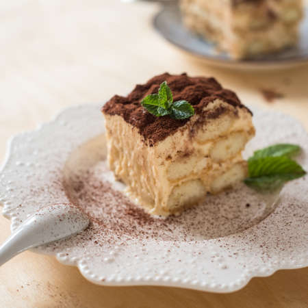 Tiramisu coffee cake served on a white plate wood background