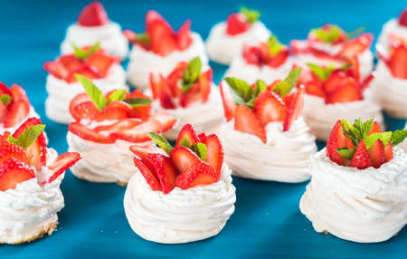 A small meringue Pavlova dessert with some strawberry slices