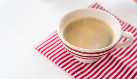 Rode koffiekopje over keuken rode stroken handdoek. Uitzicht van boven. Geïsoleerd op witte achtergrond