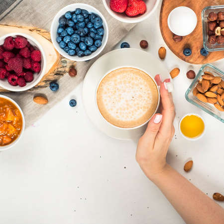 Good morning - healthy breakfast background with oatmeal coffee, berries, egg, nuts. Coffee, hands, hold, cup. White wooden food background, top view