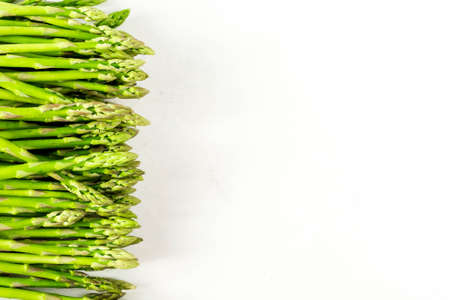 Fresh green asparagus shoots pattern, top view. Isolated over white. Food background asparagus top view pattern