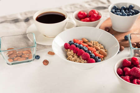 Good morning - healthy breakfast background with oatmeal coffee, berries, egg, nuts. White wooden food background,