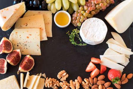 Degustazione di formaggio con frutta, bacche sul vecchio cheeseboard nero. Alimento per il vino e romantico, delicatessen di formaggio. Disegno del menu orizzontale. Vista dall'alto. spazio per il testo Archivio Fotografico - 86949184