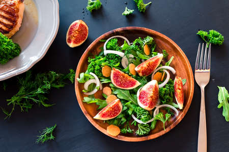 Autumn salad of arugula, figs in a brown earthenware plate on a dark background. top view