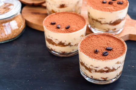 luxurious dessert Tiramisu in a glass with coffee beans on a dark background
