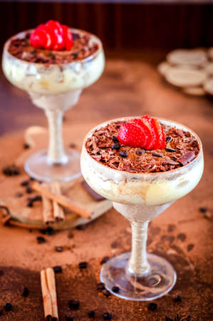 luxurious dessert Tiramisu in a glass with coffee beans and strawberries