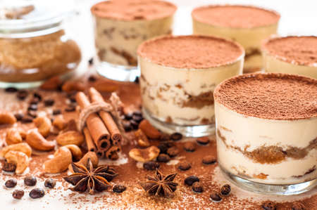Homemade tiramisu, traditional Italian dessert in glass on white wooden table