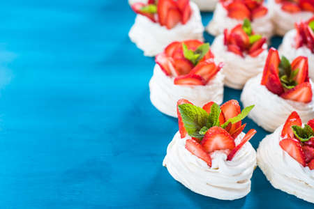 Homemade small strawberry pavlova meringue cakes blue background