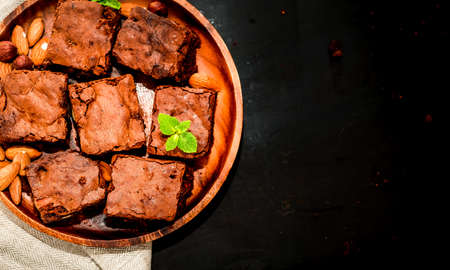brownie chocolate cake on a wooden plate top view, space for text