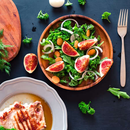 Autumn salad of arugula, figs in a brown earthenware plate on a dark background. top view, healthy and delicious food