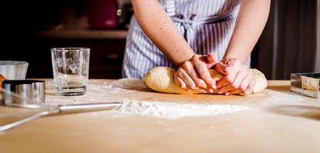 Vrouwelijke handen die deeg voor de toebehoren van de pizzakeuken maken Stockfoto