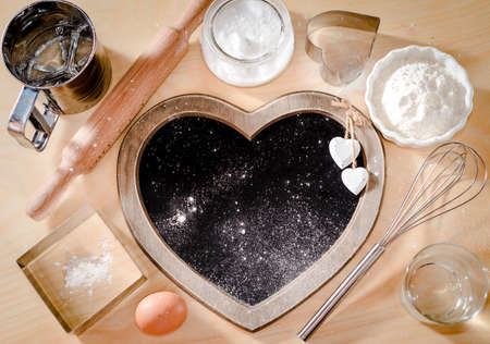 Baking ingredients background, board in the form of heart, baking concept, I love to cook, I love oven cakes, menus, bakery, bread, view from high angle, top view