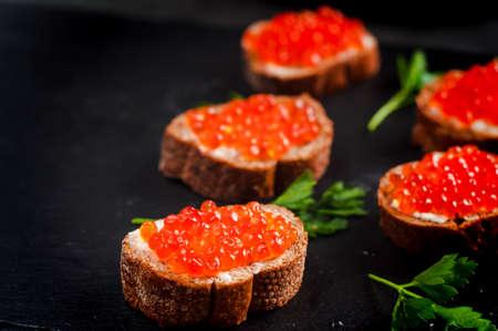 バターと黒のパンのキャビア。健康食品。魚の前菜。暗い背景 写真素材