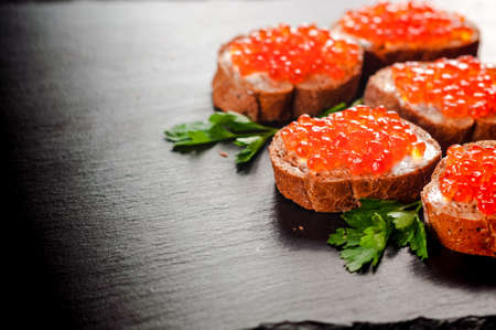 red caviar on black bread with butter. Healthy food. Fish appetizer.