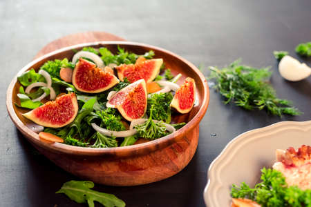 Autumn salad of arugula, figs in a brown earthenware plate on a dark background. Stock Photo