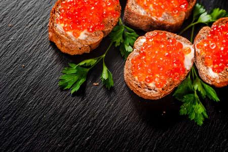 Rode kaviaar op leisteenachtergrond.
